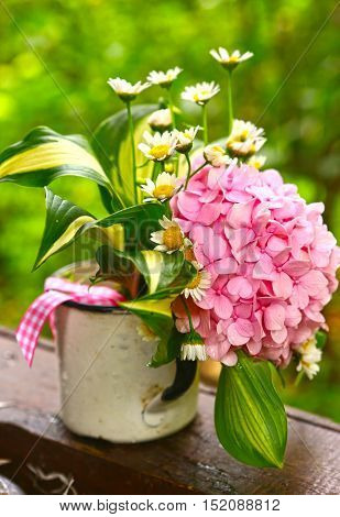 cute bouquet with hydrangea and chamomile flowers close up phtot on the green garden background