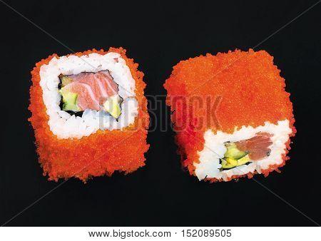 Salmon tobiko rolls on a black background