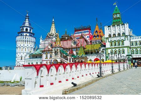 The richly decorated bridge leading to the entrance gate of Izmailovsky Kremlin decorated with towers and weathervanes Moscow Russia.
