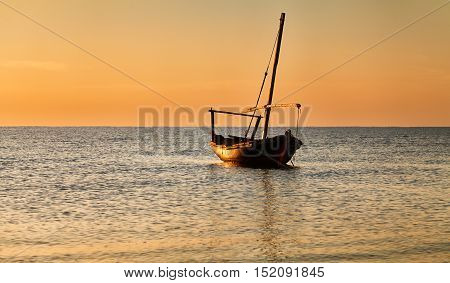 Beautiful Sunset Over The Sea. A Small Fishing Boat.