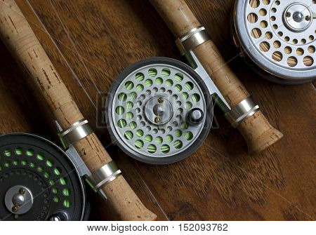 3 Vintage Fly Fishing Reels with Fly Rods in flat lay design on wooden background
