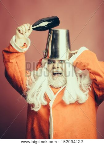 New year man with crazy face has long white beard and hair in red santa claus christmas coat and hat holding silver pail and wine bottle on studio background