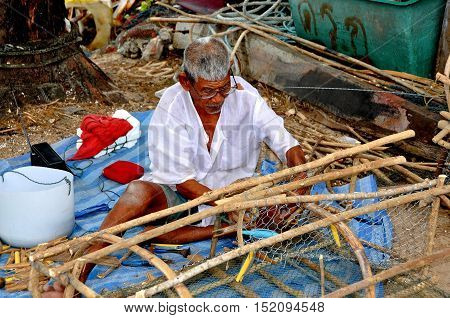 Chao Lo / Phuket Thailand - January 5 2011: An elderly Thai fisherman sitting on the ground repairs netting on a fish trap