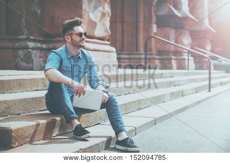 Live life bright. Cheerful content smiling man holding tablet and expressing gladness while resting on the footsteps