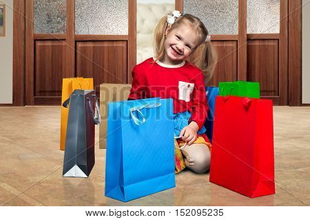 Happy little gHappy little girl and a lot of shopping bags. A child on the floor in the apartment. Shopping bags colorful brightirl and a lot of shopping bags. A child on the floor in the apartment. Shopping bags colorful bright