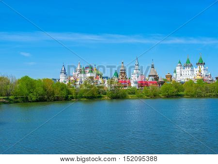 The view on Izmailovsky Kremlin complex with colorful tower and domes across the pond in the nearest garden Moscow Russia.