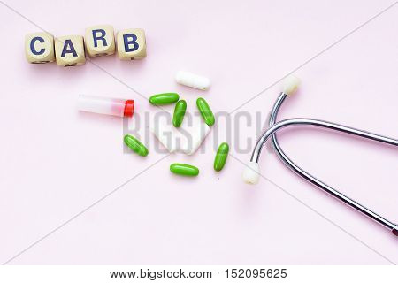 Pink background caption carb, pills and stethoscope