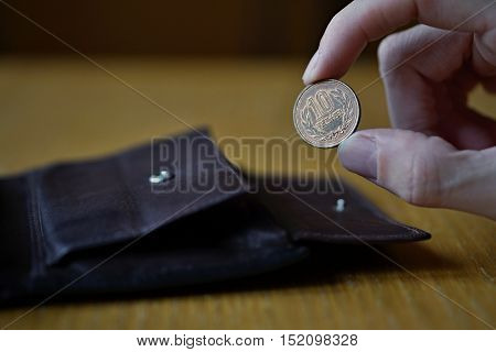 Male hand holding a bronze coin of ten Yens (Japanese Yen, JPY) and withdrawing that from the brown leather wallet