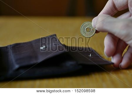 Male hand holding a bronze coin of five Yens (Japanese Yen, JPY) and withdrawing that from the brown leather wallet