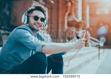 Full of joy. Cheerful handsome smiling man sitting on the footsteps and listening to music while resting in the street