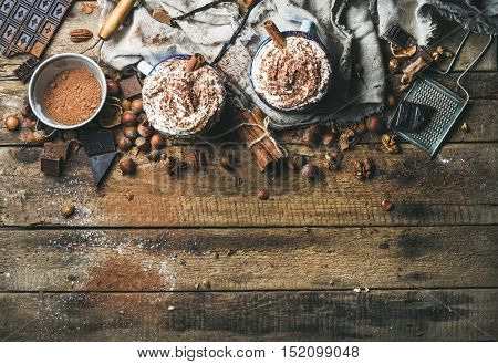 Hot chocolate with whipped cream and cinnamon sticks served with anise stars, different nuts and cocoa powder on rustic wooden background, top view, selective focus, copy space, horizontal composition