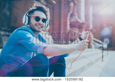 Enjoy sunny weather. Cheerful glad young man smiling and listening to music while resting on the footsteps