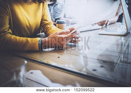 Working process in modern office.Woman looking to her mobile phone and sitting at the wooden table.Horizontal photo, blurred background. Closeup photo