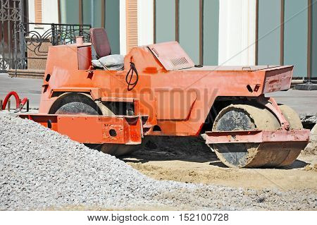 Red asphalt paver on road construction site