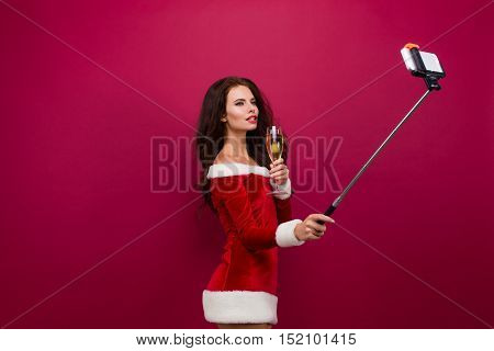 Sexy brunette woman in red christmas dress with glass of champagne in one hand, holding selfie stick in other hand, and taking self portrait. Isolate.