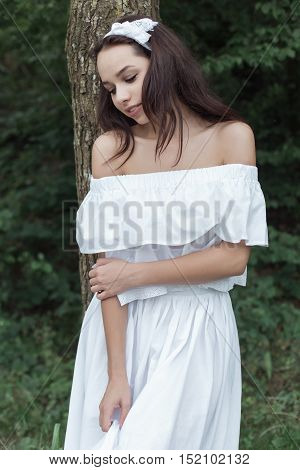 beautiful sweet girl with dark hair in a white sundress standing near a tree in the forest on hot summer day