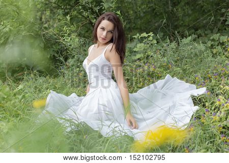 beautiful young brunette woman in a white sundress sitting in the grass near the forest on a hot summer day