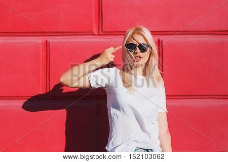 Rebel expressions and people concept - teenage girl in white t-shirt and shades showing middle finger over red bright color wall