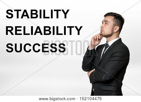 Cropped portrait of a businessman thinking with 'stability, reliability, success' words beside him. Professional motto. Durability, strength, firmness. Ideas and concepts.