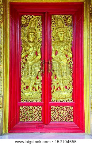 Buddhist church doors with wood carving of Thai traditional art.