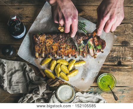 Man eating roasted pork ribs with garlic, rosemary, green herb sauce, fried potato and dark beer on rustic wooden table. Man' s hands holding fork and knife and cutting meat into pieces, top view