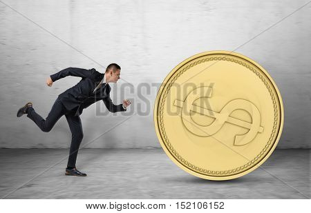 Young businessman running to catch a big golden coin. In the pursuit of success. Being motivated by money. Trying to earn.
