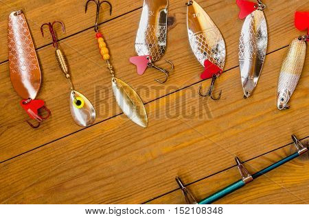 Fishing accessories for summer consisting of tackle bait lure jig hook net. Wooden background. Outdoor activity and leisure concept.