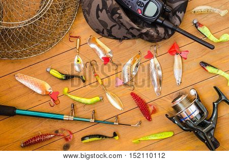 Fishing accessories for summer consisting of tackle bait lure jig hook radio reel net. Wooden background. Outdoor activity and leisure concept.