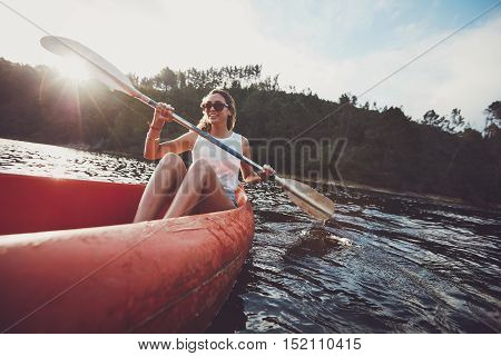 Young woman canoeing in a lake. Woman paddling kayak on a summer day.