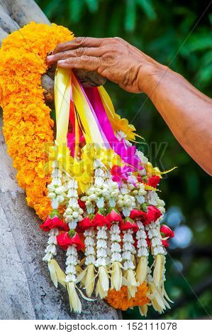 Hand on a bunch of garland to hand of Buddha image statue to pay respect.