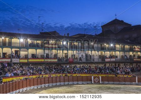 Chinchon Spain - October 15 2016: Plaza square Mayor of Chinchon adapted as a bullring Detail of balconies illuminated dressed with the Spanish flag beautiful sunset at Chinchon Spain