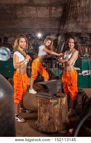 Sexy blacksmith women in orange pants are working in the workshop.