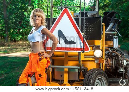 Sexy woman worker in overalls. Road sign on the background.