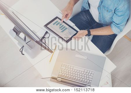 Check it out. Ambitious hardworking concentrated man doing his work while checking statistics and coding