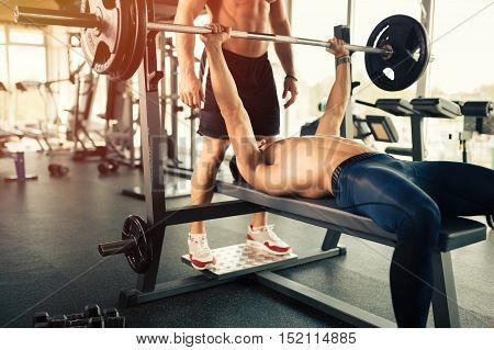 Muscular bodybuilder bench press workout in a modern gym