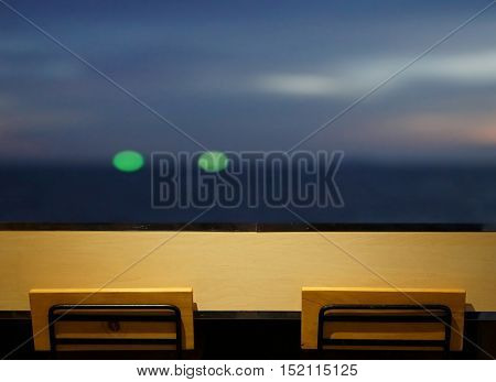 wooden long bar table top with 2 simple chairs at window with seascape at night with bokeh light from fisherman boat faraway as background