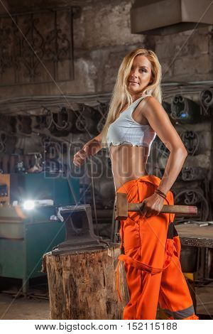 Sexy Blond Woman In Orange Pants Is Working With The Hummer And Anvil