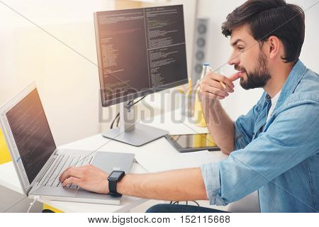 Thinking about it. Delighted young concentrated programmer working on a laptop and coding while sitting in an office.