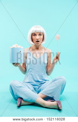 Surprised blonde young woman sitting and holding marshmallows and magic stick