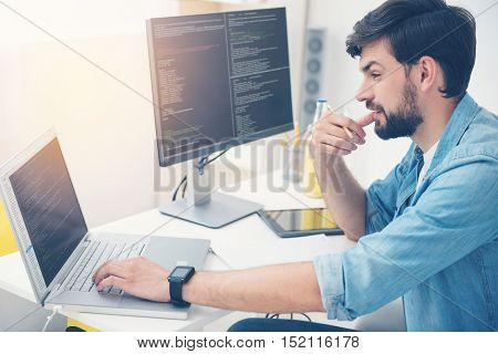 Much work to do. Young handsome concentrated programmer working in an office while using a laptop and coding.