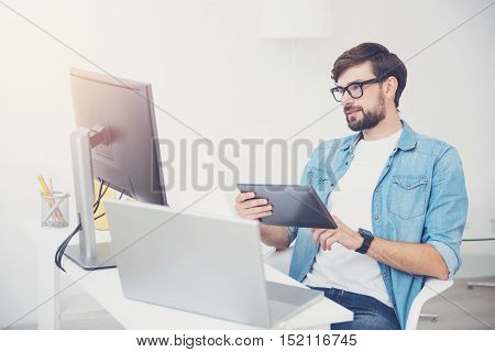 Check what is done. Handsome young successful programmer wearing a glasses and doing his work while sitting in an office with a tablet.