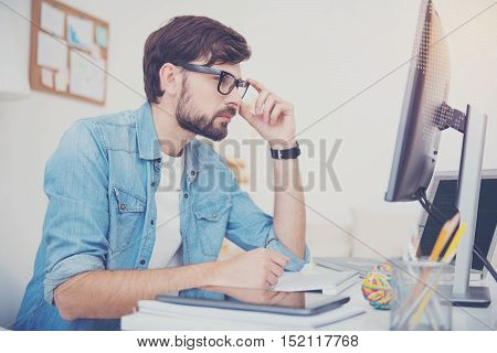 What is the point. Young handsome concentrated programmer squinting at the computer monitor and coding while working in an office.