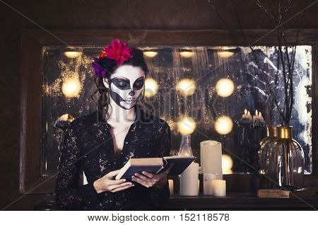 Young beautiful woman painted face as skeleton. Halloween or calavera theme