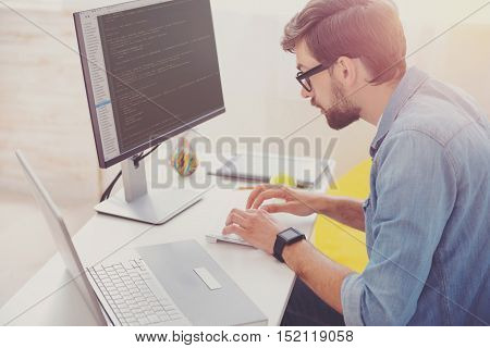 Without any mistake. Concentrated enthusiastic young programmer coding while using computer and laptop working in an office.