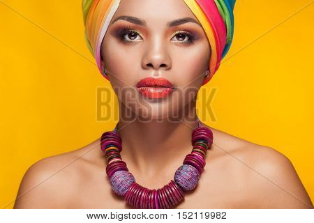 Afro American Girl In National Turban Over Yellow Background
