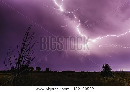 Lightning in the sky at night with a city in the distance