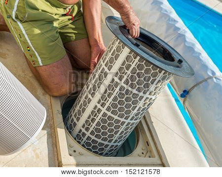 Cognac, France - July 22, 2013: A retired man in shorts and topless takes care of the maintenance of his private swimming pool. Cartridge pool filter