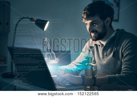 Relax and play. Delighted handsome young man drinking beer and playing videogames while using a laptop.