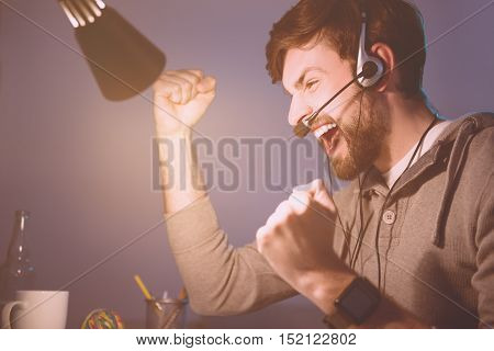 I won. Happy smiling handsome man playing videogame and winning it while wearing headphones.