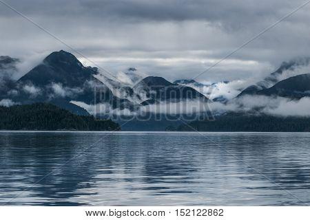 Mist hangs in mountains as sun breaks Tofino British Columbia Canada